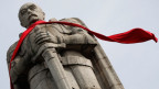 Eine steinerne Statue von Otto von Bismarck. Die Statue trägt einen roten Schal um den Hals.