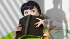 Eine Frau schaut verängstigt hinter einem Buch hervor.