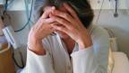 Frau im Krankenhausbett stützt mit den Händen ihren Kopf.