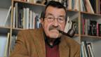 Günter Grass vor einem Bücherregal mit einer Tabakpfeife im Mund.