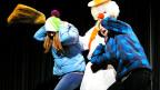 Ein Schneemann packt zwei Jugendliche.