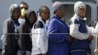 Fünf Flüchtlinge stehen hintereinander auf einem Schiff.