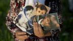 Eine Mutter zeigt Fotos ihres verstorbenen Mannes und Söhne.