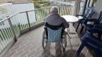 Ein Mann sitzt in einem Rollstuhl auf einem Balkon. Er ist mit dem Rücken zum Betrachter.