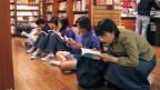 An einer Buchmesse in Taiwan: Leute spazieren durch die Hallen, wo Bücher verkauft werden.
