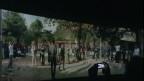 """Ein Besucher sieht sich im polnischen Pavillion den Film «Halka/Haiti 18°48'05""""N 72°23'01""""W» an."""