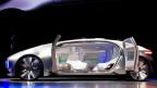 Ein selbstfahrendes silbernes Automodell mit geöffneten Seitentüren, im ausgeleuchteten Innern fehlt Lenkrad und Fahrersitz.