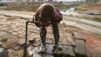 Ein Junge trinkt Wasser von einem Wasserhahnen.