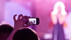 Filmen mit Smartphone während einem Konzert.