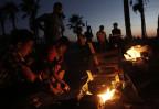 Flüchtlinge machen ein Feuer. Im Hintergrund geht die Sonne unter
