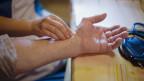 Eine junge Hand liest am Handgelenk einer älteren Frau den Puls.