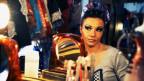 Frau in der Garderobe mit Handspiegel.