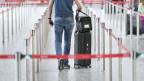 Ein Mann am Flugenhafen, einen Koffer hinter sich herziehend.