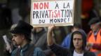 Ein Demonstrant mit einem Schild auf dem steht: Non à la privatisation du monde.