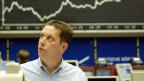 In einer Börse: Ein Mann schaut angespannt in die Höhe. Im Hintergrund eine Wachstumskurve.