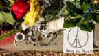 Blumen, eine ausgebrannte Kerze und eine Skizze mit den Worten: «Peace for Paris»