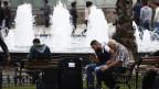 Syrische Flüchtlinge in Istanbul auf Parkbänken sitzend