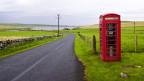 Einge englische Telefonkabine steht in einer einsamen Landschaft.
