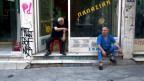 Zwei Männer sitzen vor einem Laden und sprechen miteinander.