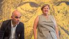 Eine Pressekonferenz: Ein Mann und eine Frau vor gelbschwarzem Hintergrund, auf dem zwei Augen zu sehen sind.