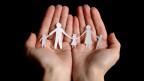 Zwei Hände, die eine Papierfamilie tragen.