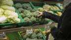 Eine Gemüseauslage, eine Frau greift nach einem Brokkoli.