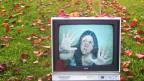 Altes Fernsehgerät liegt auf dem Rasen. Der Bildschirm zeigt eine Frau, die mit den Händen gegen die Scheibe drückt.