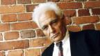 Der franzoesische Philosoph Jacques Derrida lehnt an einer Wand.