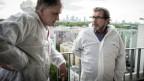 Zwei männer in weissen Anzügen stehen auf eine Terrasse.