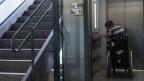 Mann im Rollstuhl fährt Lift in seine Wohnung