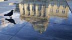 Das Bundeshaus spiegelt sich im Wasser auf dem Bundesplatz.