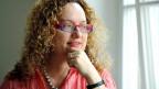 Eine Frau mit blonden Locken und zweifarbiger Brille