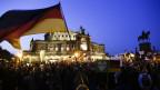Eine Menschenenmenge demonostriert vor dem Opernhaus in Dresden, im Vordergrund eine Deutschland-Fahne.
