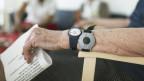 Der Arm einer älteren Dame, die zwei Uhren trägt, aber nur eine ist für die Zeit da