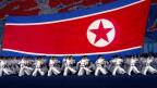 Personen in weisser Kleidung marschieren in Reih und Glied. Sie tragen eine riesige Flagge Nordkoreas.