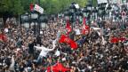 Menschenmenge. Einige Leute halten Tunesien-Fahnen.
