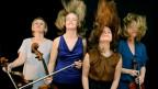 Vier Frauen stehen mit ihren Geigen auf der Bühne und schütteln ihre langen Haare.