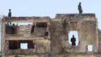 Die Ruinen eines Gebäudes, darauf und darin stehen Soldaten.