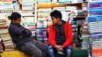 Zwei Jungs sitzen vor einem Berg Bücher.