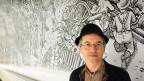 Der Comickünstler Joe Sacco vor einem von ihm gestalteten Wandgemäld am U-Bahnhof Montparnasse.