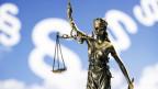 Symbolbild: Eine Justitiastatue, im HIntergrund ist das Paragrafenzeichen zu erkennen.