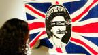 Eine Frau betrachtet einen «Union Jack» der mit der Queen und «God Save the Queen» verziert wurde.