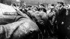 Demonstrante stehen vor einer gestürzten Stalin-Statue.