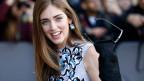 Eine Modebloggerin wird an einer Fashionshow fotografiert. Sie winkt in die Kamera.
