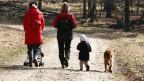 Zwei Frauen spazieren mit einem Kind.