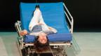 Szenebild aus dem Stück «While I Was Waiting», eine Frau liegt verkehrt auf einem Spitalbett.