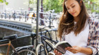 Eine Frau liest vor einer Gracht.