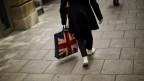 Eine Frau mit einer Tasche, auf die die britische Flagge gedruckt ist.