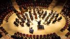 Konzertsaal in dem das Orchester mitten im Publikum spielt.