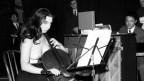 Charlotte Moorman spielt oben ohne und mit einer Geige als Bogen Cello.